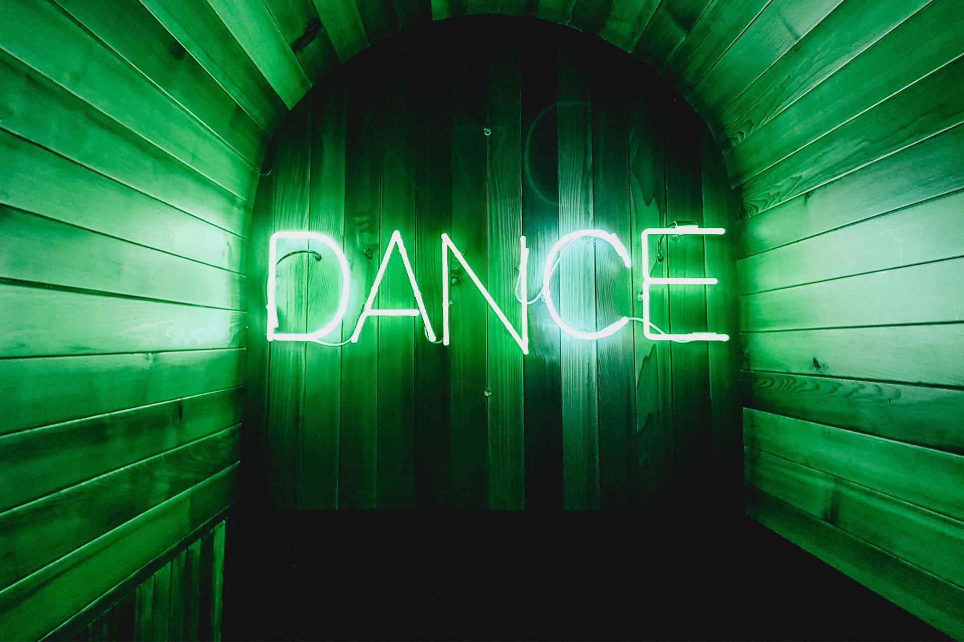 """das Wort """"DANCE"""" als leuchtender Neonschriftzug in grün"""